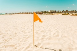Flag on the beach in the gold coast.Pure yellow soft fine sand on a Sunny sea beach.an an orange flag will be stuck in it to keep the wind at a distance.clear blue sky.summer holidays