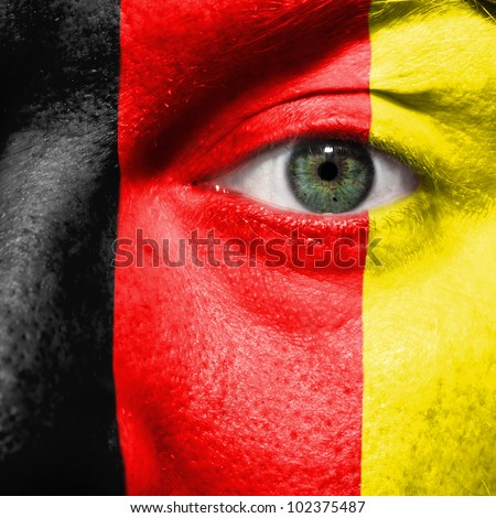 Flag painted on face with green eye to show Belgium support in sport matches