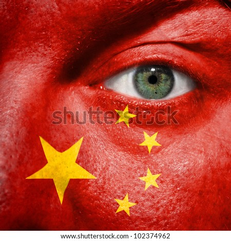 Flag painted on face with green eye to show China support in sport matches