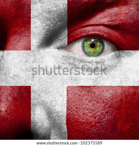 Flag painted on face with green eye to show Denmark support