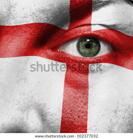Flag painted on face with green eye to show England support in sport matches - stock photo