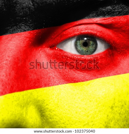 Flag painted on face with green eye to show Germany support in sport matches