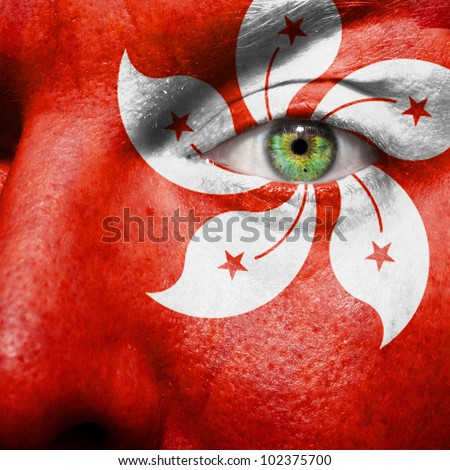Flag painted on face with green eye to show hongkong support