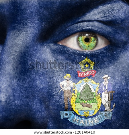 Flag painted on face with green eye to show Maine support