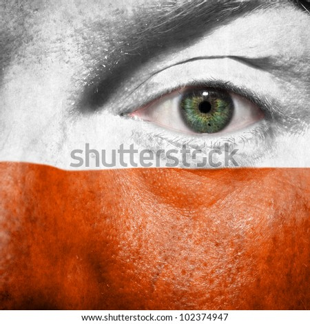 Flag painted on face with green eye to show Poland support in sport matches
