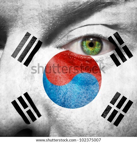 Flag painted on face with green eye to show south korea support