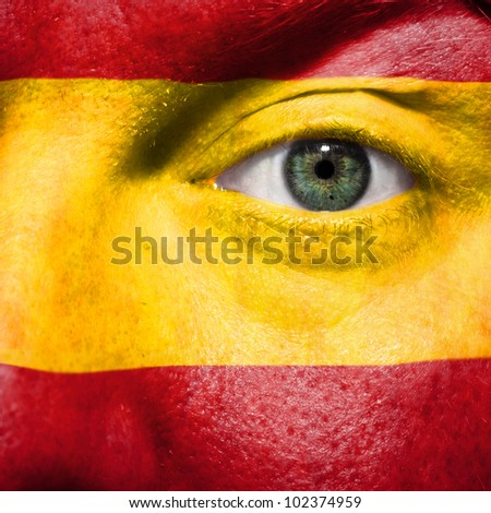 Flag painted on face with green eye to show Spain support in sport matches