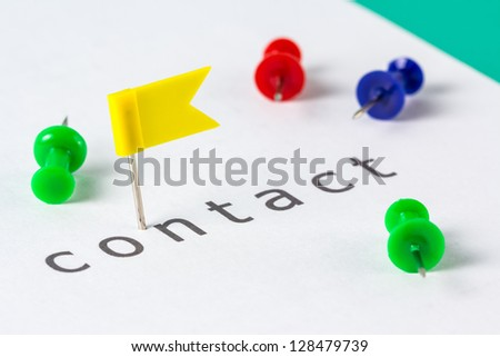 Flag push pin on paper at contact word
