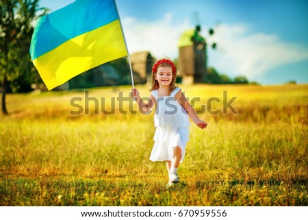 Flag Ukraine in hand little girl in wreath of red poppies. Child carries fluttering blue and yellow flag of Ukraine against background of mills in Pirogovo. #670959556