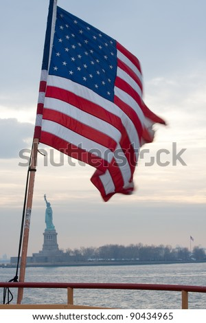 Flag whipping in the breeze in front of statue of liberty through the mist at sunset.