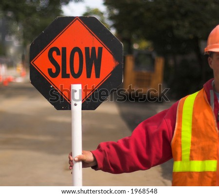 "Flagger directing traffic, holding ""Slow"" sign"