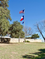 Flagpole at the Lyndon B Johnson National Historic Site in Stonewall, Texas. Three flags fly: American, Texas and flag with the LBJ Ranch branding logo.