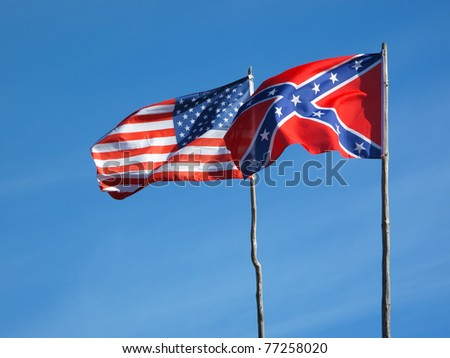 Flags of American civil war. Union flag and Confederate flag under blue sky.