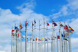 Flags of different countries of the world are flying in the wind under the blue sky