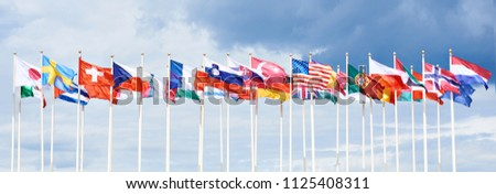 Flags of different countries on high flagpoles