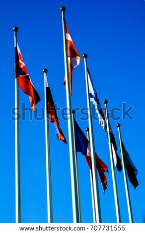 Flags of different countries on the background of blue sky #707731555
