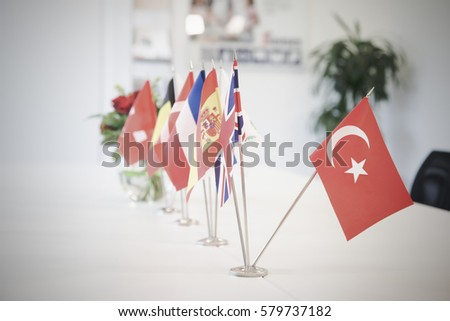 Flags of different countries on the background of the white table. Selective focus. Shallow depth of field. Toned. #579737182
