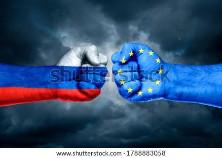 Flags of EU and Russia painted on two fists on sky background. EU versus  Russia trade war disputes concept.