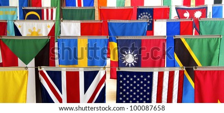 Flags of many nations hang vertically, representing a host of ethnic diversity from many cultures.