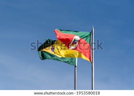 Flags of the state of Rio Grande do Sul and Brazil on blue natural background. Official symbols of the Brazilian state of Rio Grande do Sul and Brazil Foto stock ©