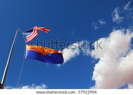 Flags of the United States and the Navajo Reservation are flying against the clouds