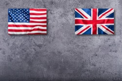 Flags of the USA and United kingdom on concrete background.