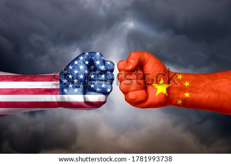 Photo of  Flags of USA and China painted on two fists on sky background. United States of America versus China trade war disputes concept.
