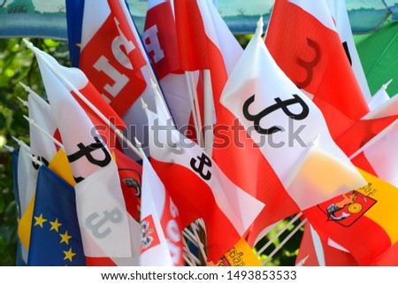 Flags of Warsaw with mermaid, Flags of Poland with Anchor (polish: Kotwica) - symbol of Fighting Poland from Warsaw Uprising and European Union Flag. Flags for sale on souvenir stand. Closeup. Zdjęcia stock ©