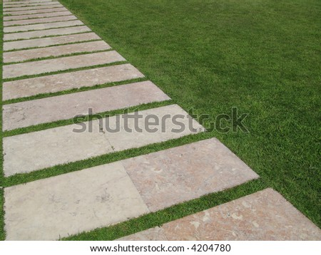 Flagstones Forming A Diagonal Path On Green Grass - stock photo