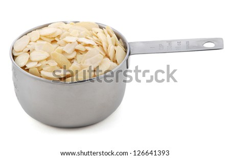 Flaked almonds presented in an American metal cup measure, isolated on a white background