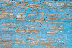 Flaking paint on wood with complimentary colours of sky blue and yellow brown. Rustic, crusty texture producing a random linear pattern like tree bark. Landscape orientation.
