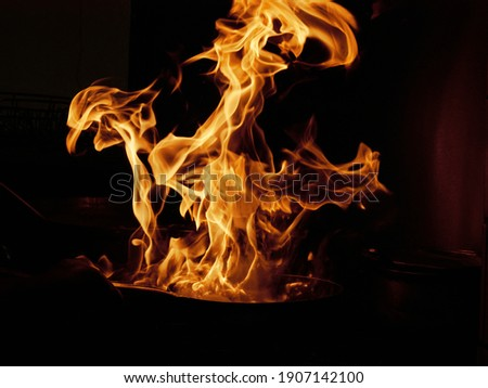 Flambe Chef Cooking in Outdoor Kitchen. Professional chef in a commercial kitchen cooking flambe style. Chef Flambe Cooking. Stock photo ©