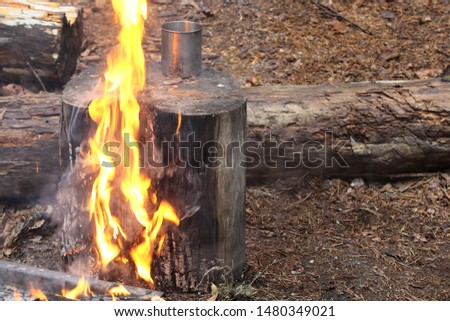 Flame burns through a log with a metal camping mug. Fire with ash and smoke on a summer day. Burning the stump with a yellow flame.Close up.Selective focus