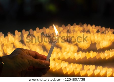 Flame glows night candles with heart-shaped bokeh on black background. #1204807738