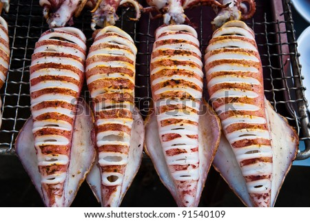 Flame grilled large squids on a bbq platform, use for seafood, health and wellness related concepts - stock photo