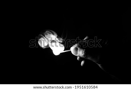 Flame lit and held between the fingers. Black and white photos. Flame lit Foto d'archivio ©