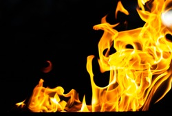 Flame of fire, saturated orange flashes on a black background. Abstract tongues of flame in the dark for design