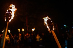 Flame on a homemade torch, fire on the background of night streets, peaceful actions with torches.