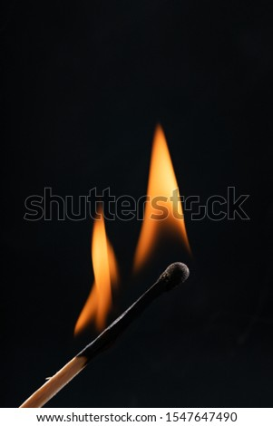Flame on a small match. Glowing match in flames. dark background.