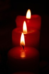 Flame red candles isolated on black background. Close up.