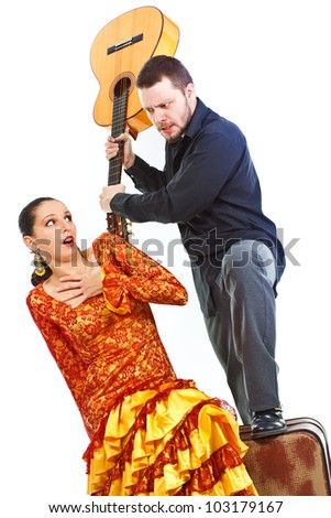 Flamenco dancer and flamenco guitarist quarelling, man holding up his guitar as if trying to hit the woman - isolated on white