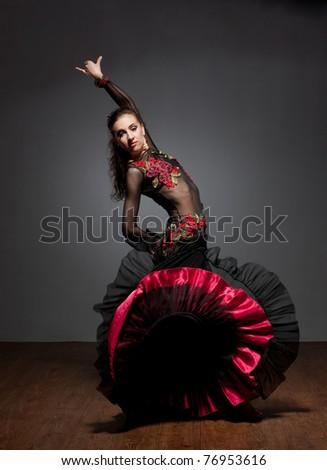 Flamenco dancer in beautiful dress on dark background
