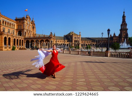 Photo of  Flamenco dancer in red dress and white spanish shawl dancing on Plaza de Espana during Feria de Abril (april fair) in Seville, Spain