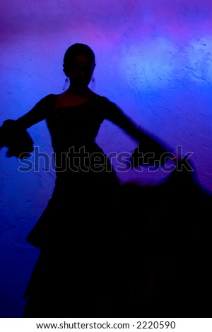 Flamenco dancer silhouette over blue background