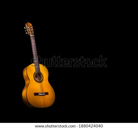 Photo of  Flamenco guitar on black background with copy space