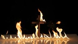 Flames on a burning cross blazing in the night