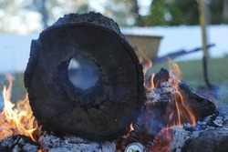 Flames spewing out a fire pit with oak wood that has been burning all day with a shovel and wheel barrow in the background.