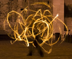 Flaming light blurs from the whirling baton on a fire dancing street performer.