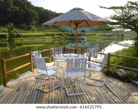 Flamingo Dai Lai Resort, Vinh Phuc, Vietnam - October 13, 2016 :  table and chairs on a jetty beside the lake at the Flamingo Dai Lai resort, Vinh Phuc Province, Vietnam #616625795