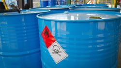 Flammable sign and dangerous sine on blue barrel tank in the storage yard of a chemical factory